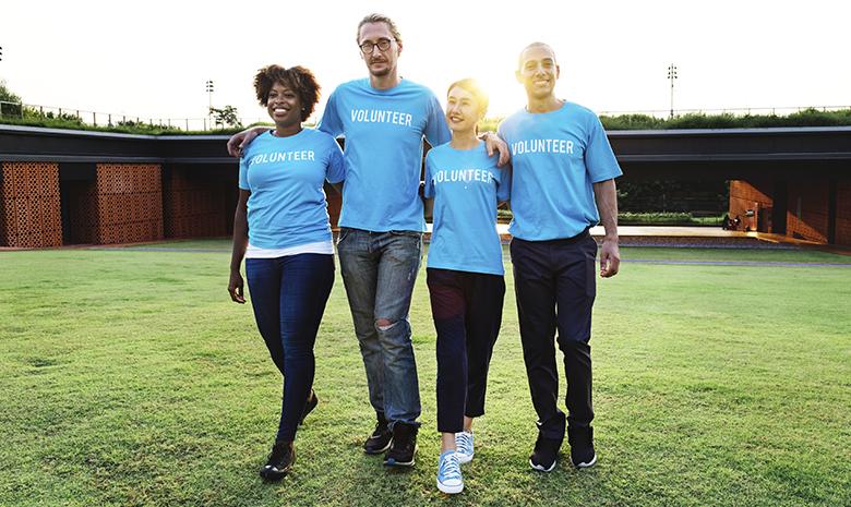 Adults wearing matching blue shirts walking arm in arm